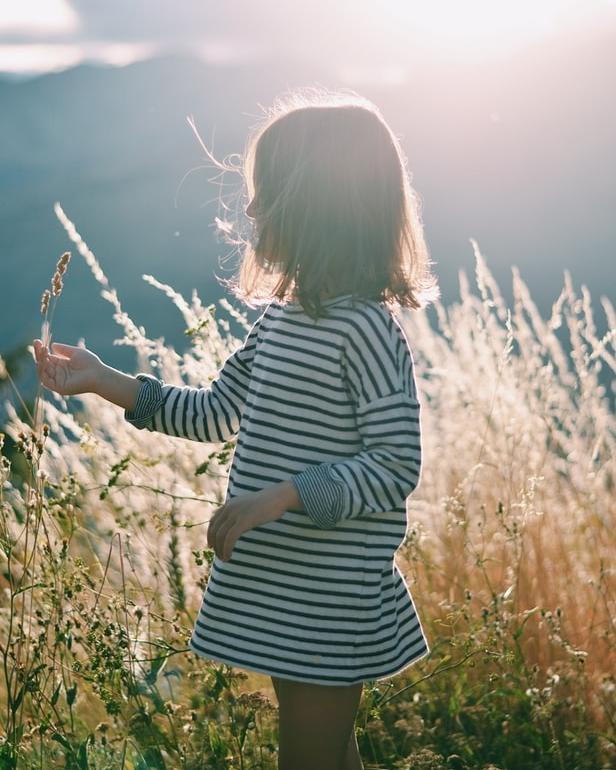 Petite fille en robe marinière dans une prairie